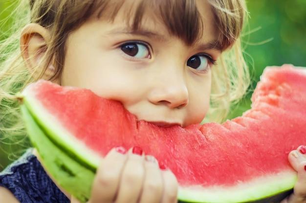 Ein kind isst wassermelone. selektiver fokus natur.
