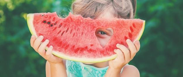 Ein kind isst wassermelone. tiefenschärfe. lebensmittel.