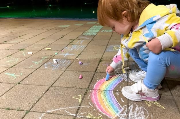 Ein kind malt an einem sommerabend vor dem haus einen regenbogen mit bunten buntstiften