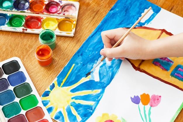 Ein kind malt haus und blumen mit farbe. tiefenschärfe