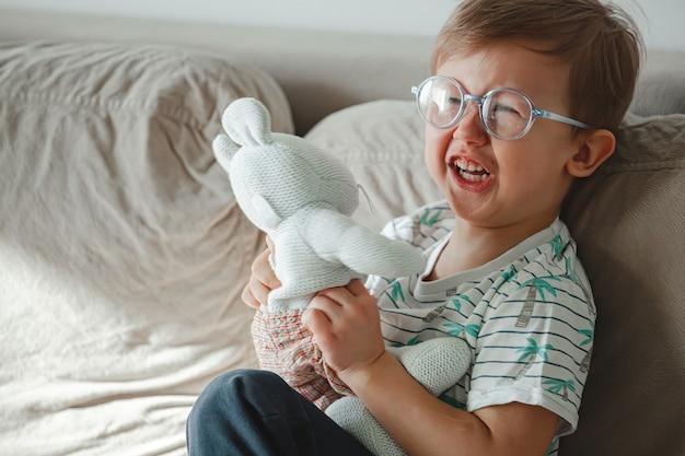 Ein kind mit autismus umarmt ein spielzeug, weint und wird wütend