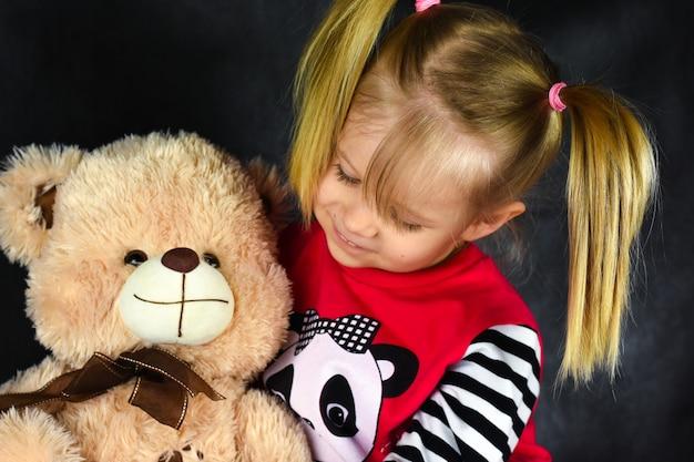 Ein kind mit einem ballon umarmt ein spielzeug eines teddybären und ist traurig und glücklich