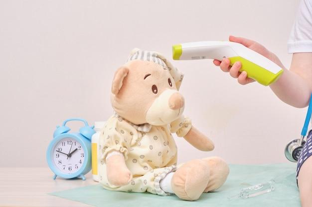 Ein kind mit misst die temperatur eines teddybären mit einem berührungslosen thermometer, ein mädchen spielt beim arzt