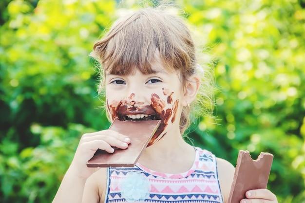 Ein kind mit süßen zähnen isst schokolade. selektiver fokus