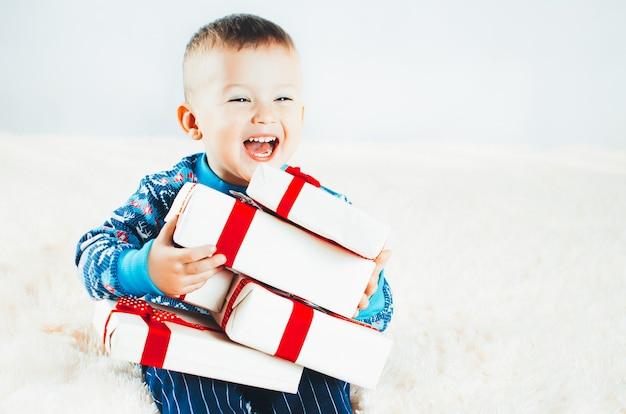 Ein kind mit vielen geschenken, silvester schreiend vor freude, es in den händen haltend