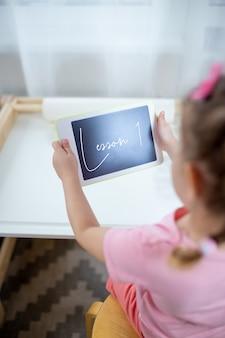 Ein kind mit weißer tablette. kind auf online-bildung, e-learning während der quarantäne. kind sieht cartoons auf tablette.