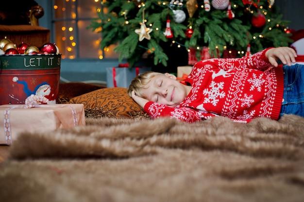 Ein kind schläft am heiligabend unter einem geschmückten weihnachtsbaum und wartet auf ein geschenk. familie feiert weihnachten zu hause. die kinder schlafen.