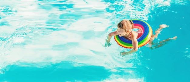 Ein kind schwimmt in einem schwimmbad mit einem rettungsring. selektiver fokus.