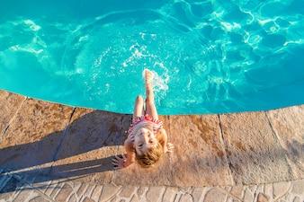 Ein Kind schwimmt in einem Schwimmbad mit einem Rettungsring. Selektiver Fokus