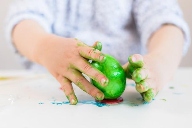 Ein kind setzt ein grünes osterei auf einen stand mit seinen händen, die mit farbe auf einer weißen tabelle befleckt werden.