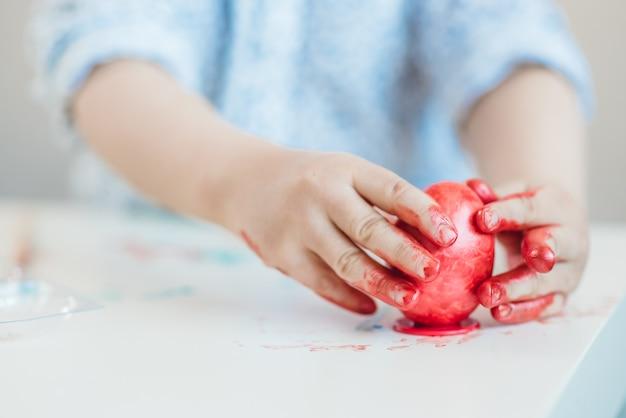 Ein kind setzt ein rotes osterei auf einen stand mit seinen händen, die mit farbe auf einer weißen tabelle befleckt werden.