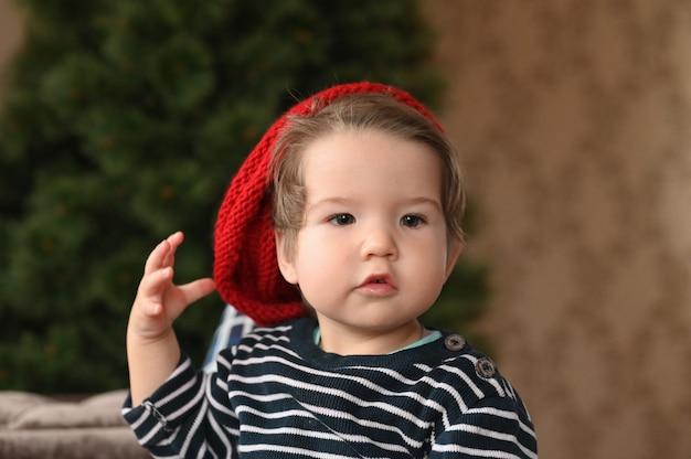 Ein kind setzt einen hut auf. ein roter hut und ein kind. zeigt einen finger. das kind ist 0-1 jahre alt. einjähriges kinderporträt.