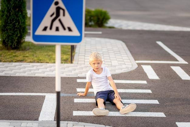 Ein kind sitzt auf der straße an einem fußgängerüberweg und hält sein bein