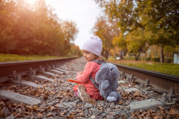 Ein kind spielt an einem sonnigen sommertag allein auf der eisenbahn, gefährlicher akt.