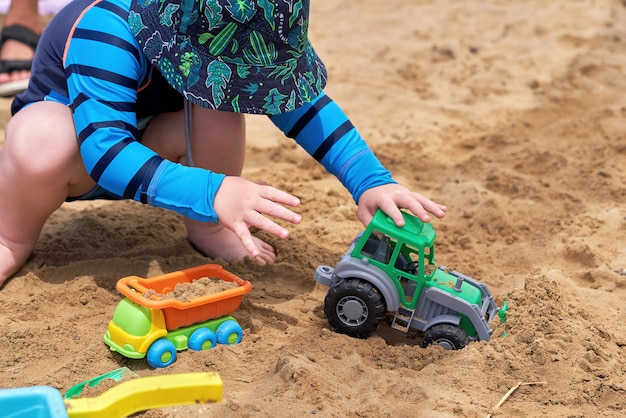 Ein kind spielt in einem spielzeugauto an einem sandstrand an einem sonnigen sommertag