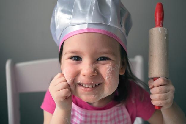 Ein kind spielt mit mehl. das mädchen bereitet pfannkuchen zu.