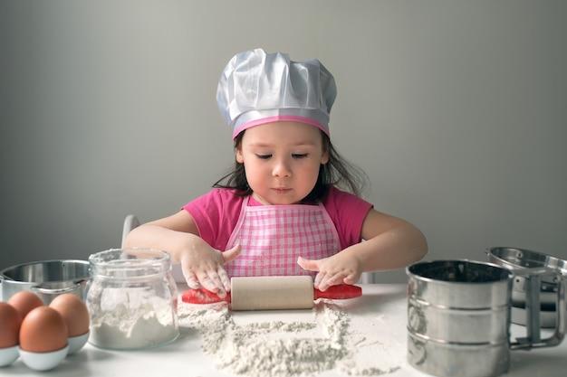 Ein kind spielt mit mehl. kleines mädchen im kochkostüm macht pfannkuchenteig.
