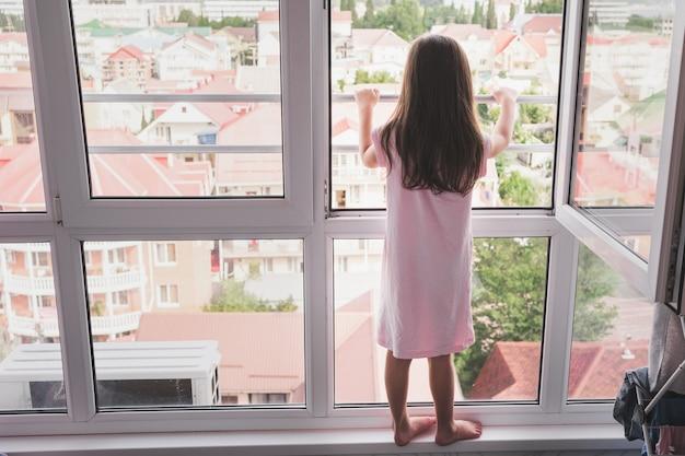 Ein kind steht gefährlich an einem offenen fenster kinder und offene fenster ein mädchen im nachtpyjama...