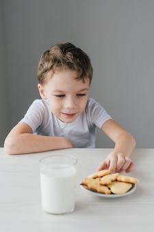 Ein kind stiehlt von einem teller mit frisch gebackenen hausgemachten keksen