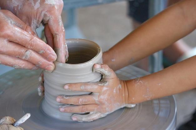 Ein kind trainiert, wie man eine keramikvase mit lehrer kippt