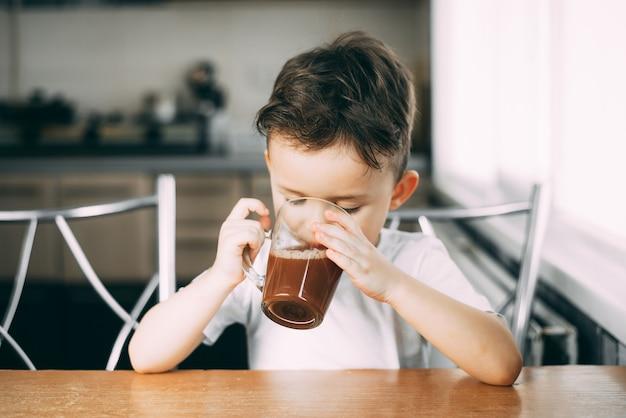 Ein kind trinkt kakao in der küche oder süße heiße schokolade bei tageslicht