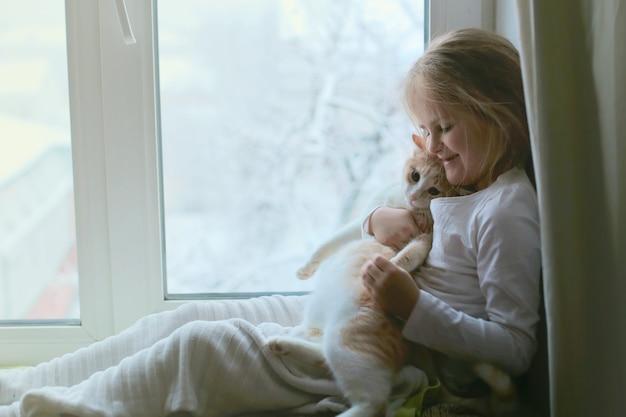 Ein kind umarmt eine katze, die auf einer fensterbank sitzt. kleines mädchen und katze sind freunde