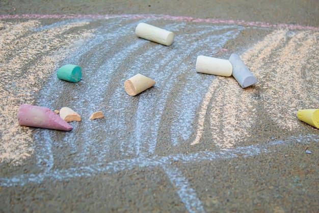 Ein kind zeichnet einen regenbogen auf den asphalt. selektiver fokus. kind.