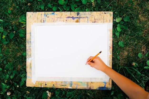Ein kind zeichnet mit einem bleistift auf ein weißes blatt papier, das an einem holzbrett befestigt ist