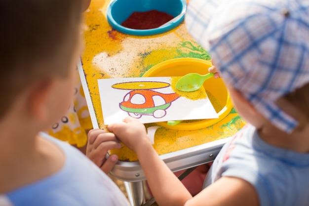 Ein kind zeichnet mit farbigem sandbild. zeichentrickfiguren.