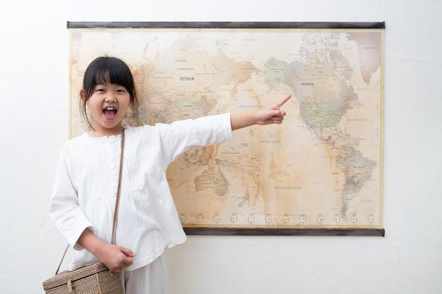 Ein kind zeigt und lacht auf die weltkarte.