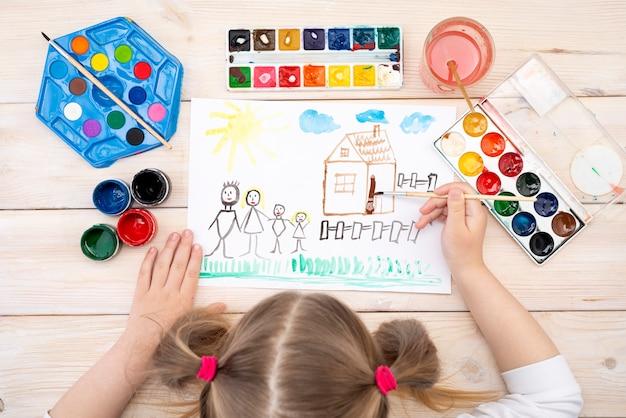 Ein kind zieht mit seiner familie eine geburtstagskarte. die zeichnung wurde von einem kind mit farbfarben angefertigt. eine glückliche familie. kinderzeichnung. von oben betrachten