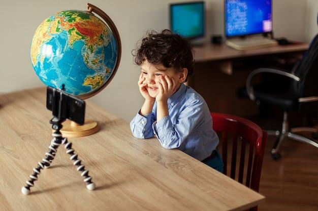 Ein kinderblogger dreht ein video auf einem smartphone auf einem stativ, der junge posiert auf einem smartphone-kamera-shoo...