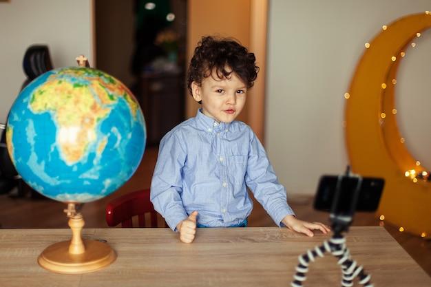 Ein kinderblogger dreht ein video auf einem smartphone auf einem stativ der junge posiert auf einer smartphone-kamera dreht einen vlog neben dem globus lustiges süßes kind