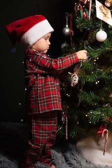 Ein kinderjunge in weihnachtsmütze und pyjama hängt ein spielzeug an den weihnachtsbaum.