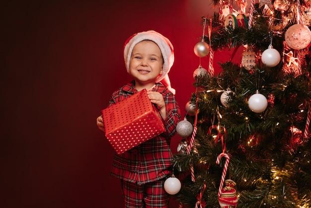 Ein kinderjunge in weihnachtsmütze und pyjama steht mit einer schachtel in der hand am weihnachtsbaum.