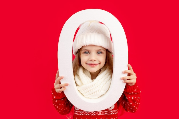 Ein kindermädchen in einer wintermütze und einem pullover mit einer großen zahl null auf einem roten, monochromen, isolierten hintergrund freut sich und lächelt, das konzept von neujahr und weihnachten, platz für text