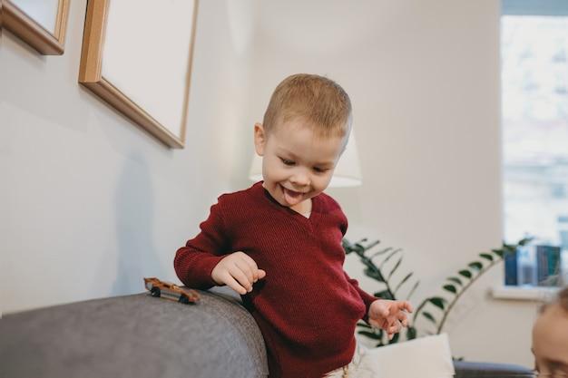 Ein kindischer kaukasischer junge mit blonden haaren spielt freudig mit seinem vater, der auf dem sofa sitzt