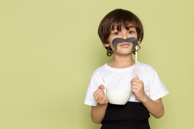 Ein kindjunge der vorderansicht im weißen t-shirt, das schnurrbart und tasse kaffee auf dem steinfarbenen raum hält