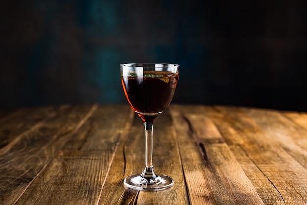 Ein klassischer saurer cocktail aus nick- und noraglas, garniert mit einem minzblatt auf einem holztisch
