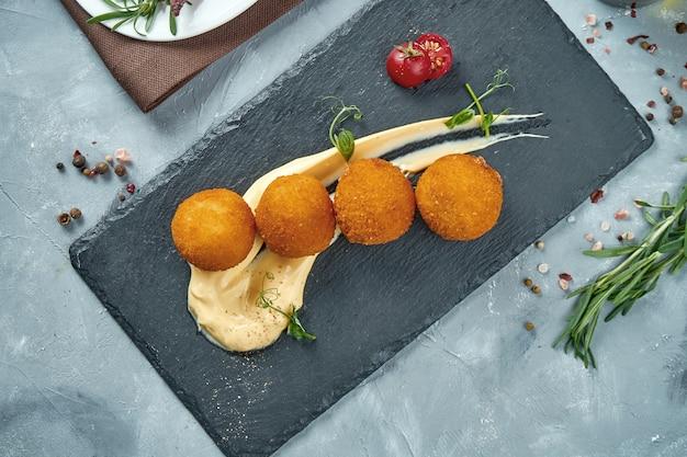 Ein klassischer sizilianischer risotto arancini snack mit verschiedenen füllungen. gefüllte frittierte reisbällchen draufsicht. essen flach lag