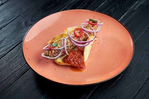 Ein klassisches orientalisches gericht ist ein gegrillter puten-lula-kebab, der in einer pita mit zwiebeln und roter sauce serviert wird. schwarzer holzhintergrund