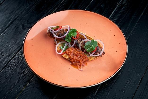 Ein klassisches orientalisches gericht ist ein gegrillter rind- oder lamm-lula-kebab, der in einer pita mit zwiebeln und roter sauce serviert wird.