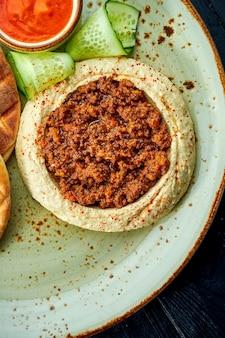 Ein klassisches orientalisches gericht - kichererbsen-hummus mit olivenöl und hackfleisch serviert mit gebackenem pita in einem holztisch