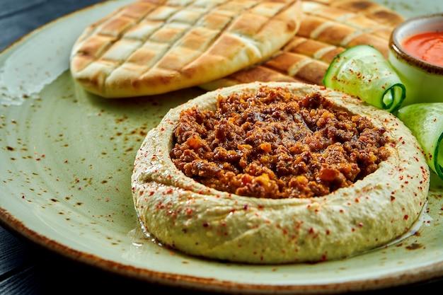 Ein klassisches orientalisches gericht - kichererbsen-hummus mit olivenöl und hackfleisch, serviert mit gebackenem pita in einem teller auf einer dunklen holzoberfläche. vegetarisches essen. diät