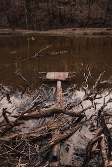 Ein kleiner alter hölzerner zerstörter pier am fluss mit weggeworfenen ästen