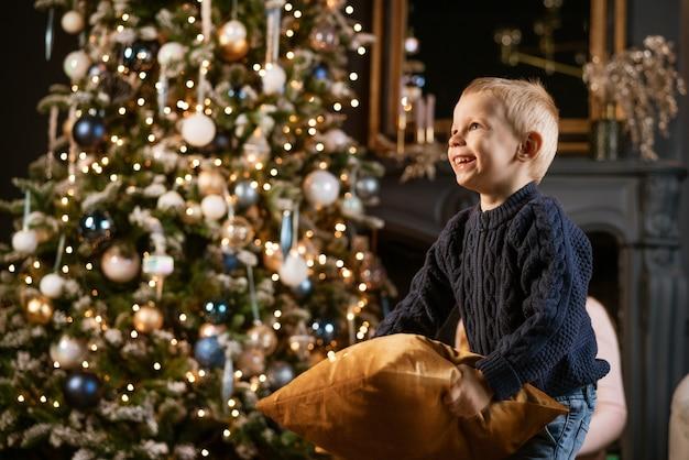 Ein kleiner blonder junge lacht und spielt mit einem kissen vor dem hintergrund eines weihnachtsbaumes...