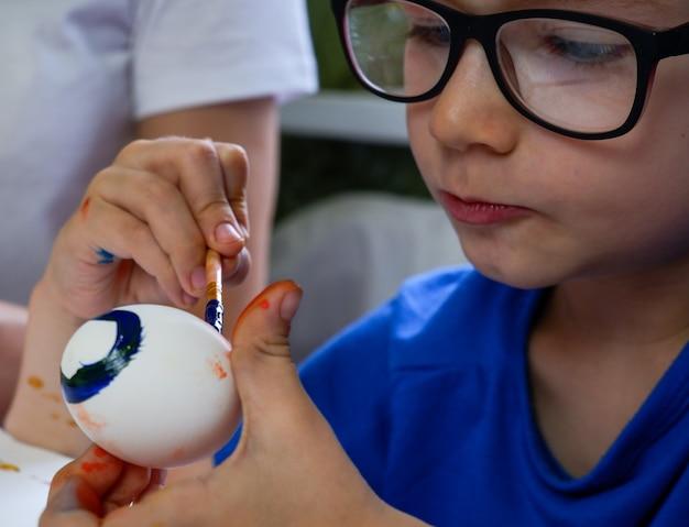 Ein kleiner blonder junge malt eier für die osterferien in der heimischen küche drinnen