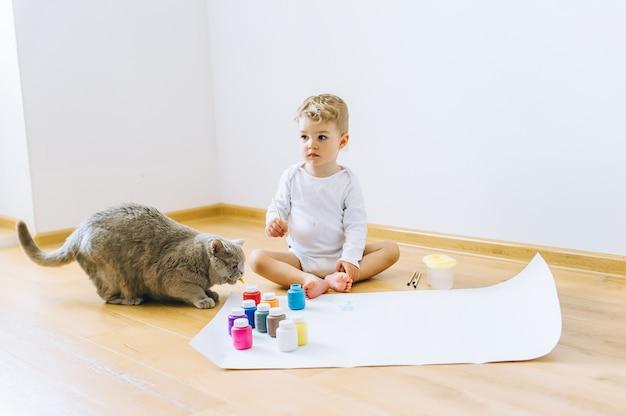 Ein kleiner blonder junge malt ein papier mit einer katze