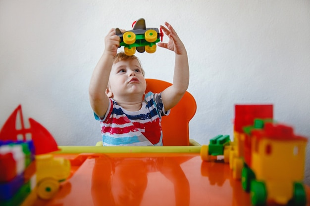 Ein kleiner blonder junge sitzt zu hause an seinem schreibtisch zwischen hellen plastikspielzeugen und spielt mit dem flugzeug, das es hochhält. hochwertiges foto