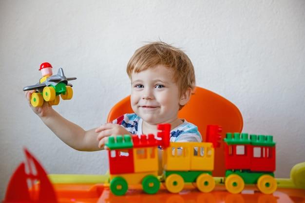 Ein kleiner blonder junge zu hause, der an einem orangefarbenen kindertisch sitzt und einen bunten plastikbausatz spielt. hochwertiges foto